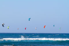 Kite Surfing in Hawaii. A bunch of people are kite surfing on the north shore of Oahu in Hawaii. This shot shows the man kites in the air with people on royalty free stock photos