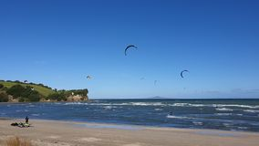 Kite surfing New Zealand. Ocean sea water wind windy waves coast shore shoreline coastline sport fun activity sail rough sand beach blue green cliff speed royalty free stock photo