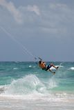 Kite Surfing in the ocean. Kite surfer jumping the waves in the ocean Royalty Free Stock Photography