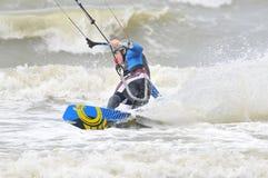 Kite surfing in spray. Surfer going kite surfing, surfboard splashes bursts of spray Royalty Free Stock Photo