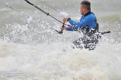 Kite surfing in spray. Surfer going kite surfing, surfboard splashes bursts of spray stock image