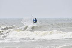 Kite-surfing in spray. Surfer going kite surfing, surfboard splashes bursts of spray Stock Photography