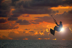 Kite surfing sunset. Kite surfer catching air and flying through the sun during a beautiful ocean sunset Stock Photo
