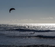 Kite surfing. A kite surfer navigates the waves on the Pacific Ocean in California royalty free stock image