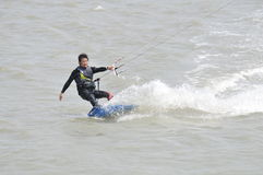 Kite-surfing in Taiwan. Surfers going kite surfing, surfboard splashes bursts of spray. Photograph on March 23, 2014 in Hsinchu, Taiwan Stock Image