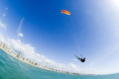 Kiteboard Big Air. Kitesurfer doing a big air jump in front of a beach and some buildings Stock Photography