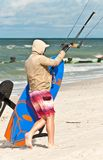 Kiteboard and cables held by young, male kiteboarder waking on sand   at a tropical beach. Extreme sport, young, male kiteboarder walking on a sandy beach, being Royalty Free Stock Photography