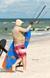 Kiteboard ed i cavi hanno tenuto da giovane, kiteboarder maschio che sveglia sulla sabbia ad una spiaggia tropicale fotografia stock libera da diritti