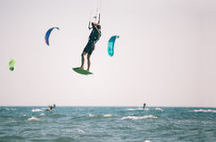 Kiteboarder athlete performing kiteboarding kitesurfing tricks. Unhooked Stock Photos
