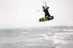 Kiteboarder athlete performing kiteboarding kitesurfing tricks Stock Photography