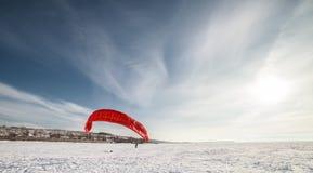 Kiteboarder avec le cerf-volant rouge Photographie stock libre de droits