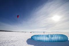 Kiteboarder with blue kite on the snow Royalty Free Stock Photography