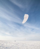 Kiteboarder with blue kite on the snow Royalty Free Stock Images