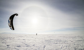 Kiteboarder with blue kite on the snow Royalty Free Stock Photos