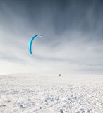 Kiteboarder with blue kite on the snow Royalty Free Stock Image