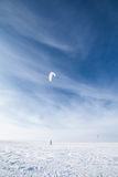 Kiteboarder with blue kite on the snow Stock Photography