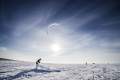 Kiteboarder with blue kite on the snow Stock Images