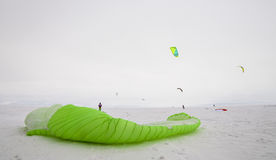 Kiteboarder with blue kite on the snow Royalty Free Stock Photo