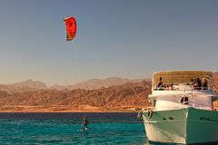 Kiteboarder enjoying surfing in blue water near the moored yacht. Travel and tourism concept royalty free stock photo
