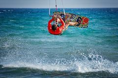 Kiteboarder, kitesurfer performing kiteboarding kitesurfing tricks on the water. Man athlete doing kiteboarding, kiteboarder jumping with the kite doing extreme stock photo