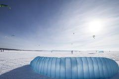 Kiteboarder met blauwe vlieger op de sneeuw Stock Foto's