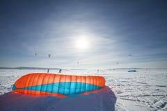 Kiteboarder mit blauem Drachen auf dem Schnee Stockbild