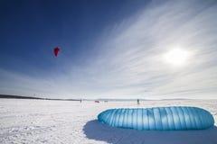 Kiteboarder mit blauem Drachen auf dem Schnee Lizenzfreie Stockfotografie