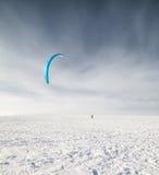 Kiteboarder mit blauem Drachen auf dem Schnee Lizenzfreies Stockbild