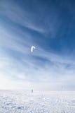 Kiteboarder mit blauem Drachen auf dem Schnee Stockfotografie