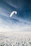 Kiteboarder mit blauem Drachen auf dem Schnee Lizenzfreie Stockbilder