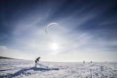 Kiteboarder mit blauem Drachen auf dem Schnee Stockbilder