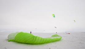 Kiteboarder mit blauem Drachen auf dem Schnee Lizenzfreies Stockfoto