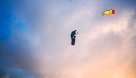 Kiteboarder performing a jump against sky Stock Photos
