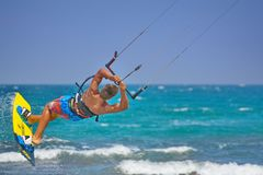 Kiteboarder performing kiteboarding jumps and tricks. Kitesurfer athlete performing kitesurfing jumping tricks. Spectacular jumps with the kite while kiting royalty free stock images