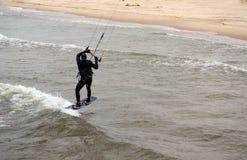 Kiteboarder sails onto the beach Stock Photo