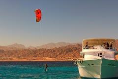 Kiteboarder som tycker om att surfa i blått vatten nära den förtöjde yachten Lopp- och turismbegrepp royaltyfri foto