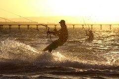 Kiteboarder sportsman under sunset sun Royalty Free Stock Images
