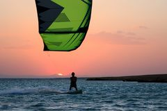 Kite boarder sportsman under sunset sun, freestyle kiteboarding rider on the evening kitesession, sunset in the sea, extreme stock image