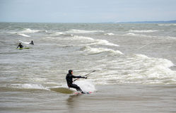 Kiteboarder and surfers Stock Photos