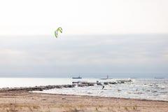 Kiteboarders som seglar fyren i havet med skepp i Arkivfoto