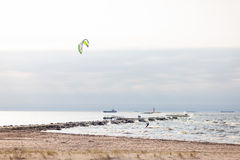 Kiteboarders to sail the lighthouse in the sea with ships in the Stock Photo