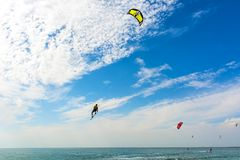 Kiteboarding. A kite surfers rides the waves. Recreational activities, water sports, hobbies and fun in summer. Artistic picture. stock image