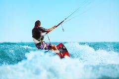 Kiteboarding Kitesurfing konkurrensar som dyker pölsportar som simmar vatten Kitesurf handling på våg Royaltyfri Fotografi