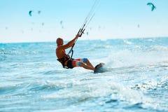Kiteboarding Kitesurfing konkurrensar som dyker pölsportar som simmar vatten Kitesurf handling på våg Arkivfoto
