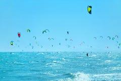 Kiteboarding Kitesurfing konkurrensar som dyker pölsportar som simmar vatten Kitesurfers i havet summa Arkivfoton