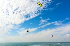 Kiteboarding Las personas que practica surf de una cometa montan las ondas Activ recreativo Imagen de archivo
