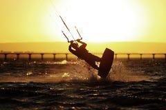 Kiteboarding sportowa sylwetka, zmierzch w morzu Zdjęcia Royalty Free