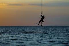 Kiter professionnel faisant un tour compliqué sur un beau fond de coucher du soleil photographie stock