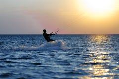 Kiter professionnel faisant un tour compliqué sur un beau fond de coucher du soleil photo libre de droits