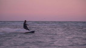 A man in a diving suit manages a training kite at dawn. Kiter sails at dawn, alone in the sea stock video footage
